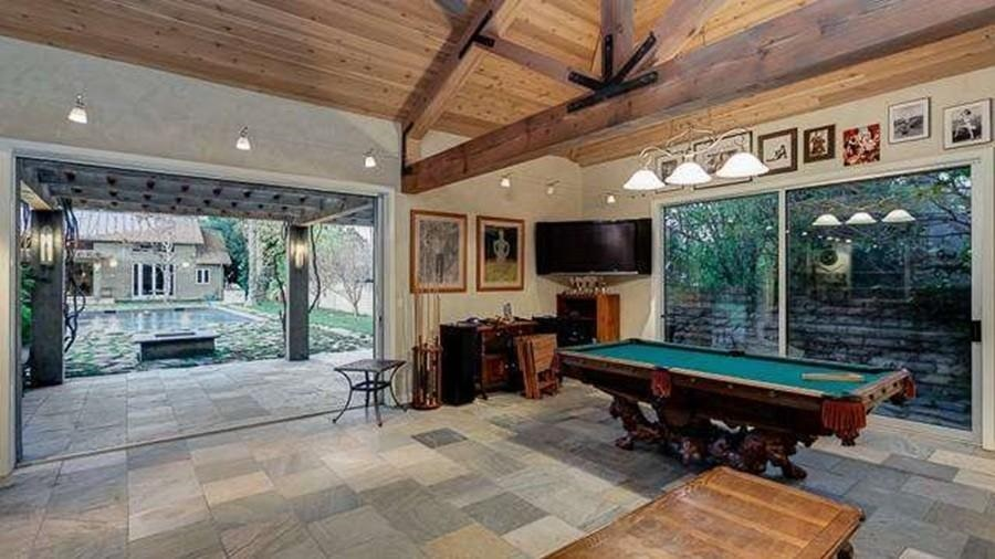 The game room has a large pool table under a row of lights hanging from the wooden ceiling with exposed beams. Image courtesy of Toptenrealestatedeals.com.