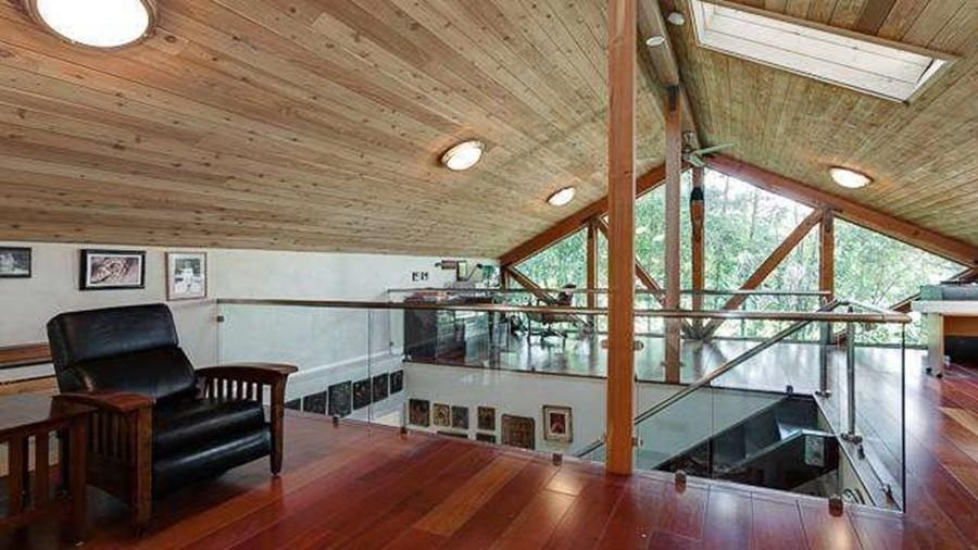 This is the second-floor indoor balcony with glass railings and a wooden cathedral ceiling. Image courtesy of Toptenrealestatedeals.com.