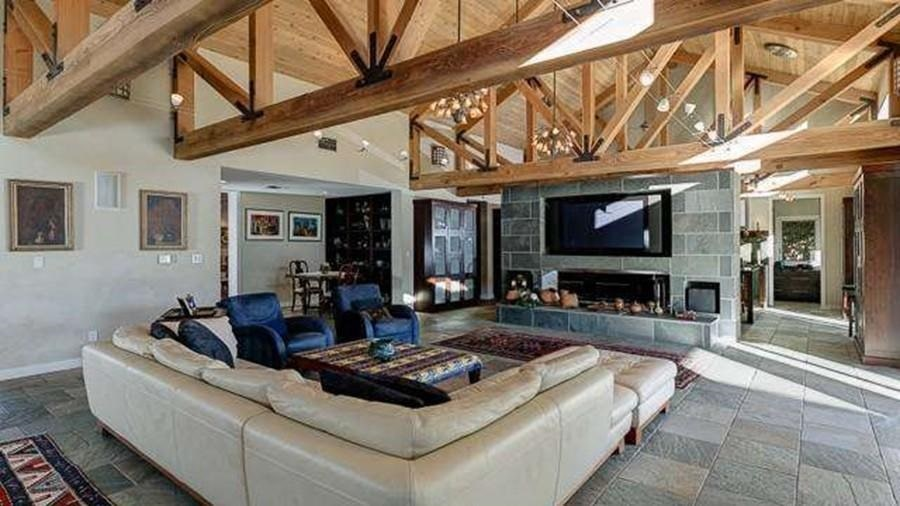 This other look at the living room shows the tall wooden cathedral ceiling with exposed wooden beams and a skylight that lets in natural lights. Image courtesy of Toptenrealestatedeals.com.