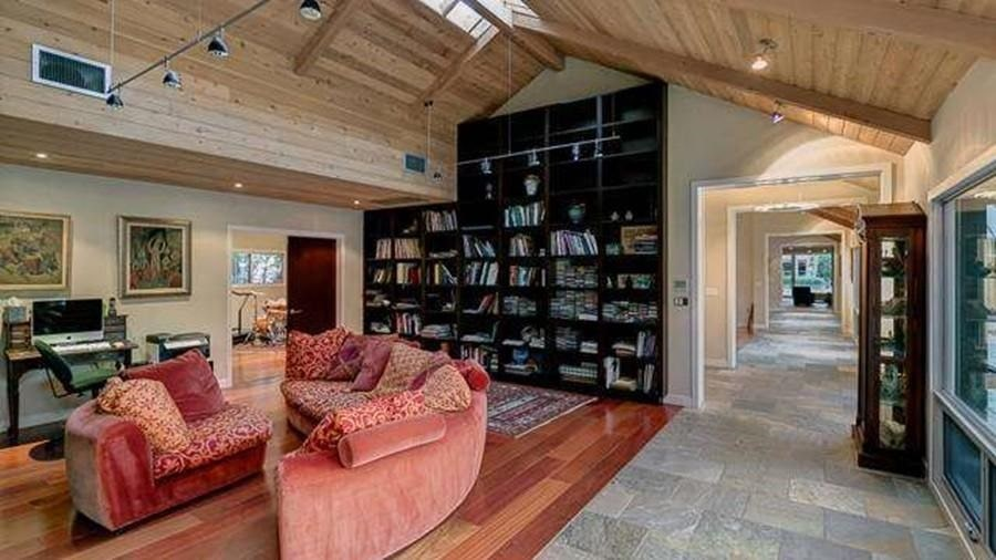 This is the home office with a large black bookshelf built into the tall wall reaching to the cathedral ceiling with a skylight. Image courtesy of Toptenrealestatedeals.com.