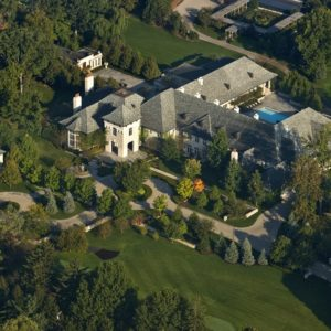 This is an aerial view of the massive mansion with gray roofs and white exteriors that stand out against the surrounding green landscape. Image courtesy of Toptenrealestatedeals.com.