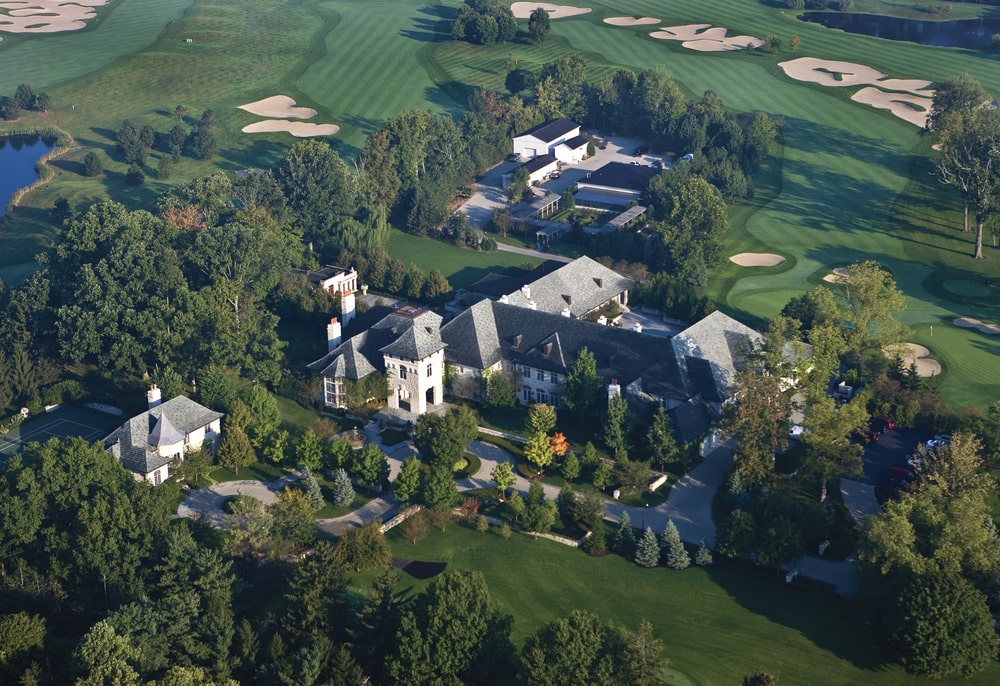 This aerial view of the mansion showcases the various outdoor amenities of the mansion along with the surrounding green landscape. Image courtesy of Toptenrealestatedeals.com.