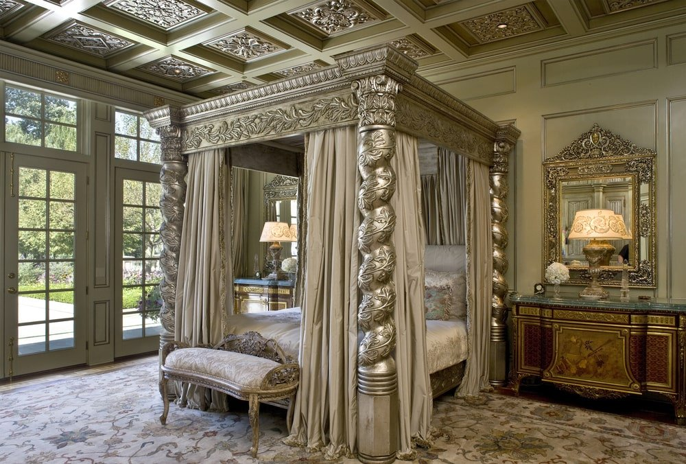 The bedroom has a large and ornate four-poster bed with a silver tone that matches the coffered ceiling. Image courtesy of Toptenrealestatedeals.com.