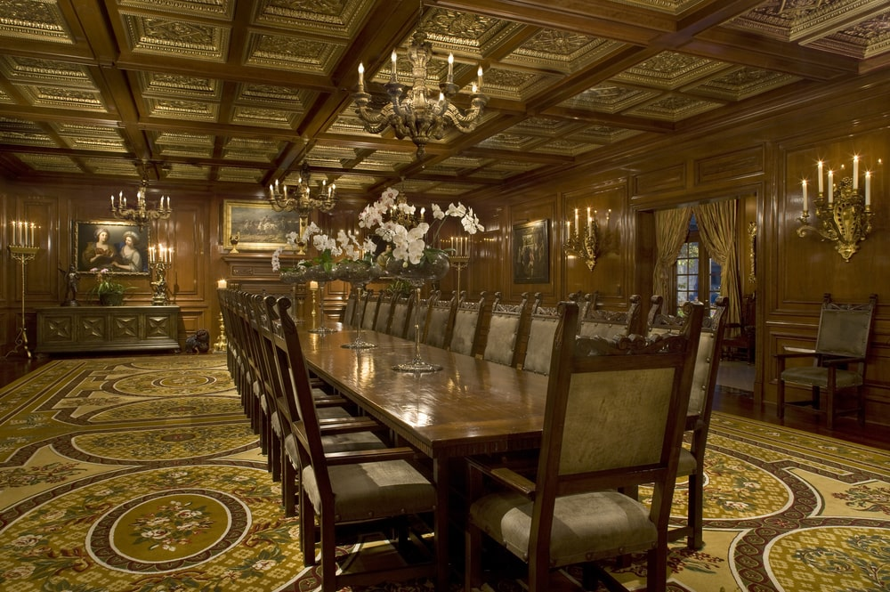 This is a massive formal dining room with a long wooden dining table paired with matching wooden chairs under a coffered ceiling that hangs a couple of chandeliers over the table. Image courtesy of Toptenrealestatedeals.com.
