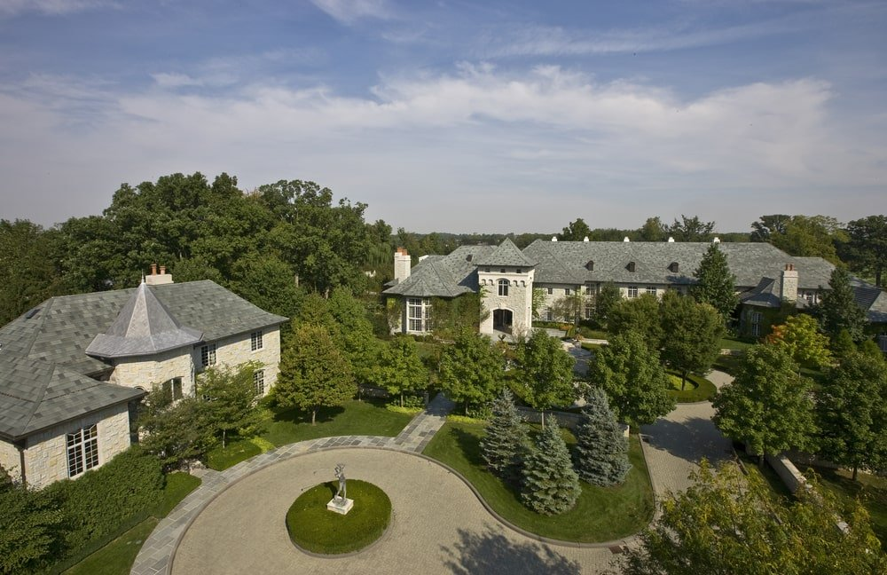 This is an aerial view of the front of the house showcasing the driveway, circular courtyard and the house exteriors complemented by the tall trees and grass lawns. Image courtesy of Toptenrealestatedeals.com.