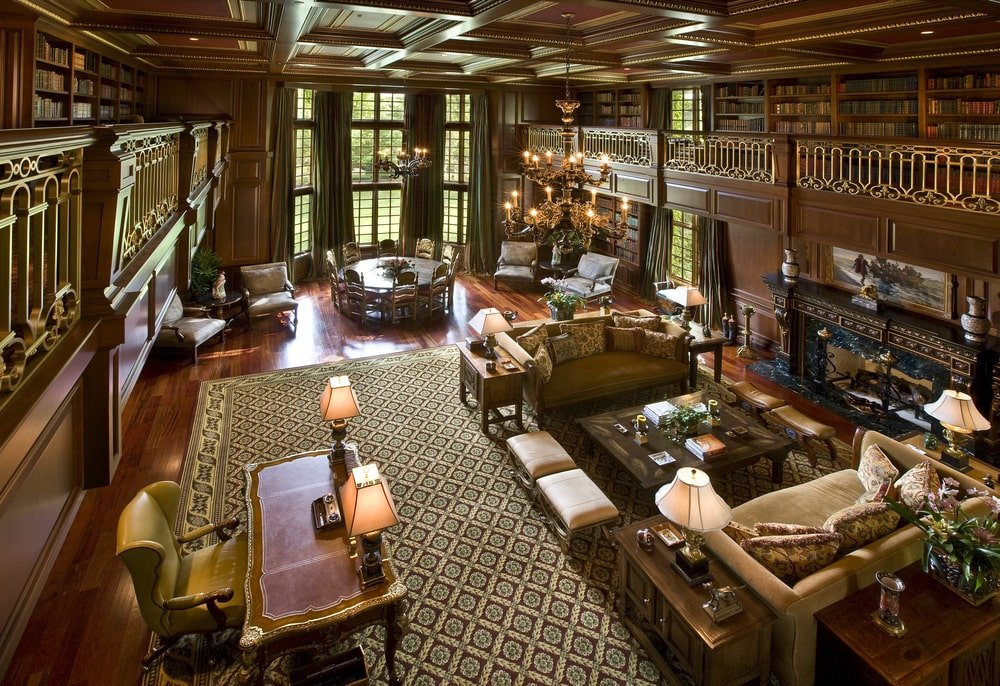 This is the spacious library with a wooden desk and various comfortable sitting areas complemented by the dark wooden tone of the walls and coffered ceiling. Image courtesy of Toptenrealestatedeals.com.