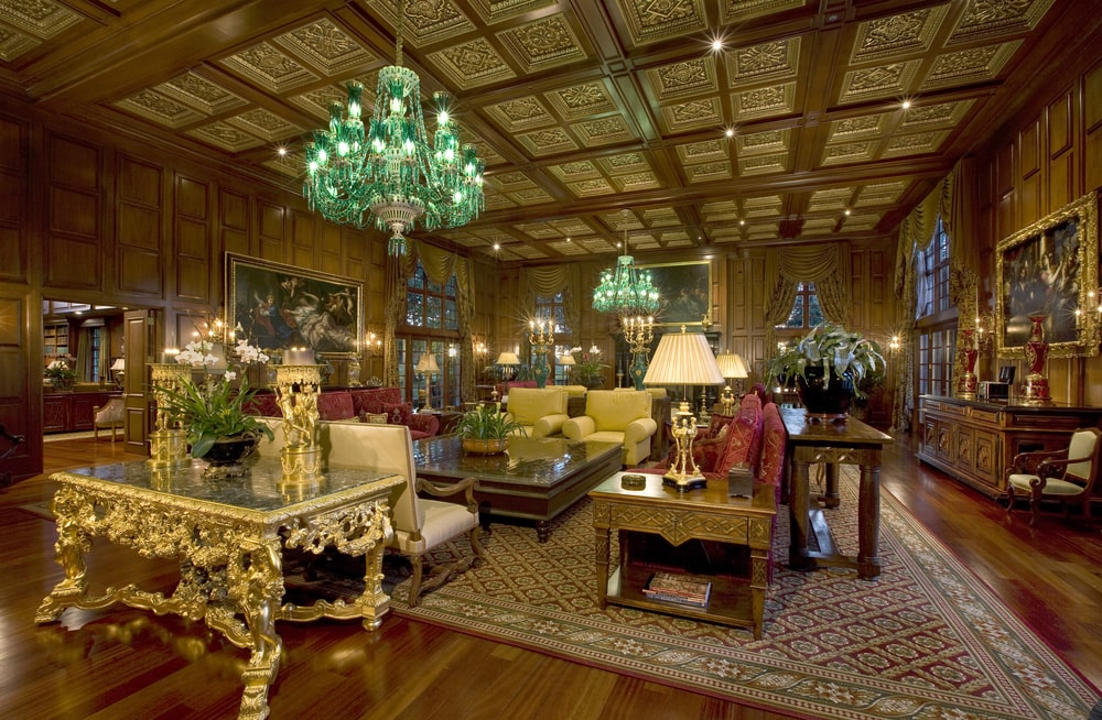 This is the luxurious living room with a tall coffered ceiling that hangs a couple of green chandeliers over the sofa set surrounding the wooden coffee table. Image courtesy of Toptenrealestatedeals.com.