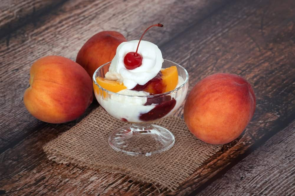 A cup of vanilla peach ice cream with a cherry on top and Melba peaches on wooden background.