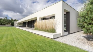 A minimalist house with a modern white exterior and a wide lawn area.