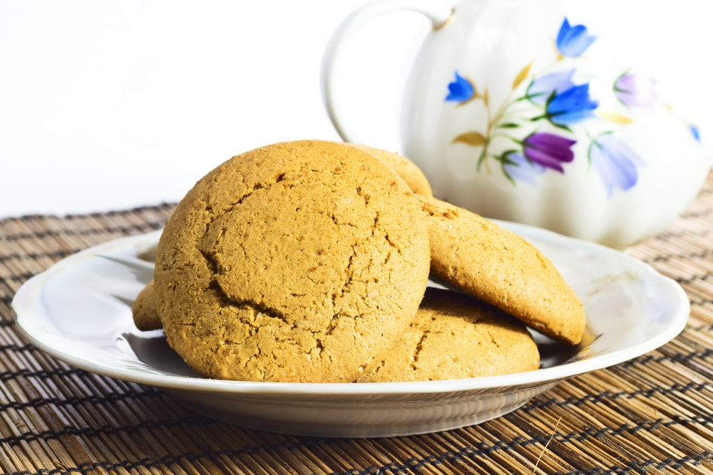 Molasses cookies on a saucer beside a pot with floral designs.