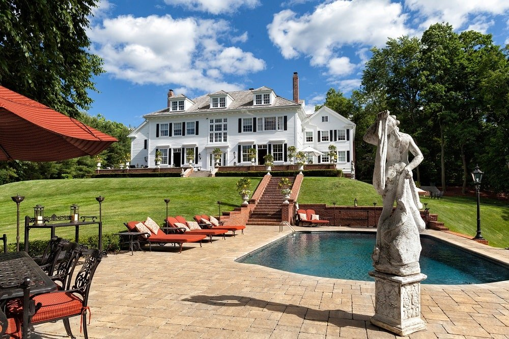 This is a look at the back of the mansion from the vantage point of the pool. Here you can see the concrete statue adorning the pool and the bright exteriors of the house complemented by the surrounding green landscape. Image courtesy of Toptenrealestatedeals.com.