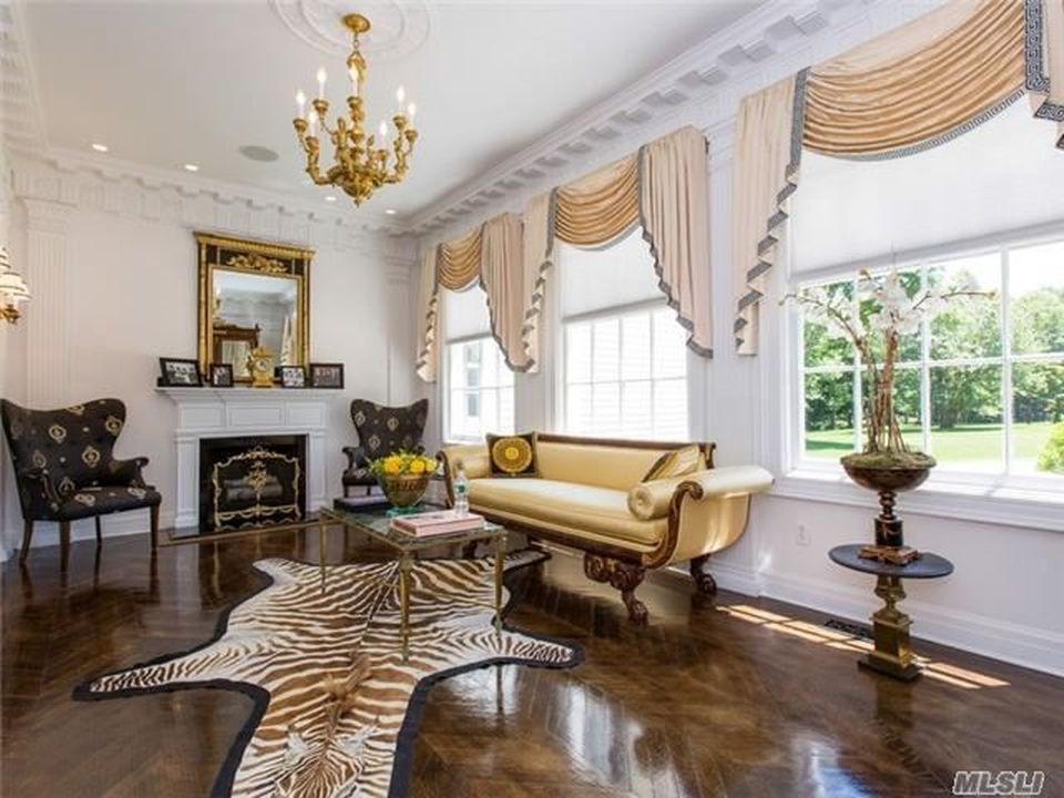 The den also has its own white fireplace that warms the beige sofa by the row of large windows with peach curtains. Image courtesy of Toptenrealestatedeals.com.