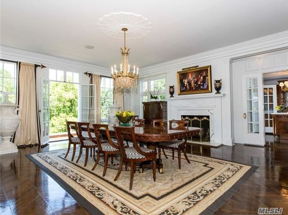This is the formal dining room with a long wooden dining table next to a large white fireplace topped with a painting. Image courtesy of Toptenrealestatedeals.com.