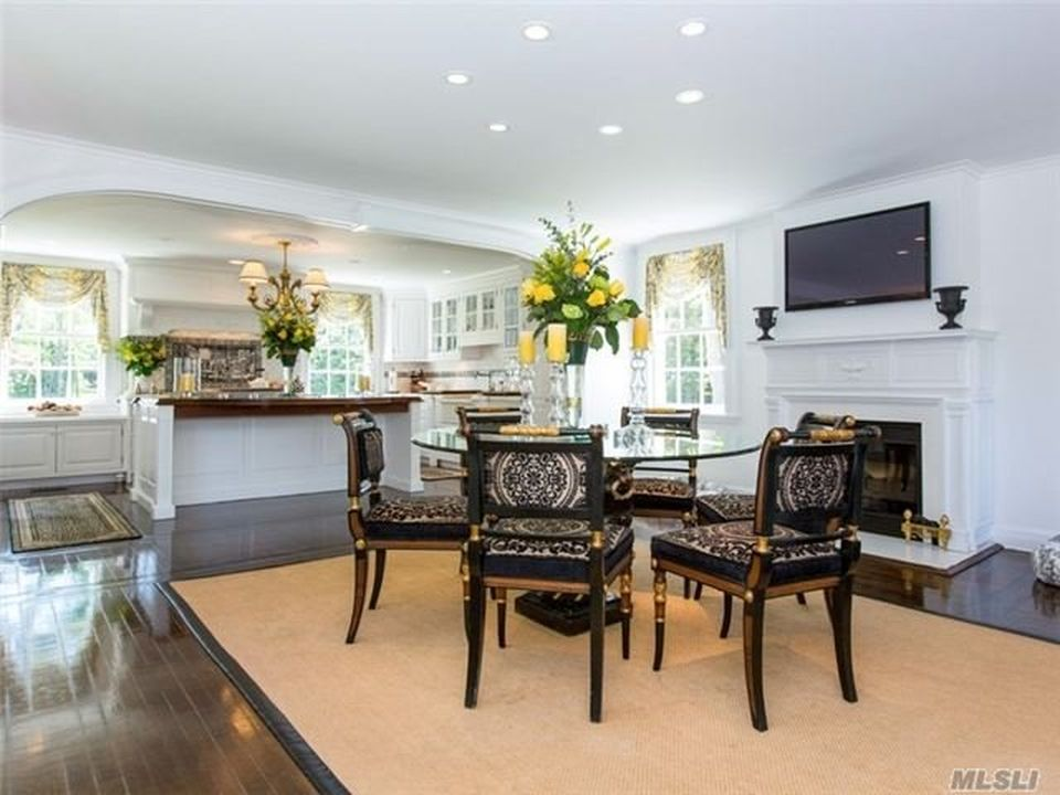 A few steps from the kitchen is this informal dining area and breakfast nook. It has a round glass-top dining table on a beige area rug. Image courtesy of Toptenrealestatedeals.com.