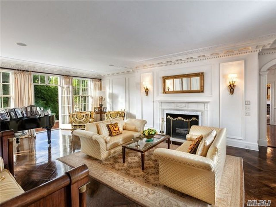 This family room has a couple of beige sofas flanking a glass-top coffee table across from the fireplace. Image courtesy of Toptenrealestatedeals.com.
