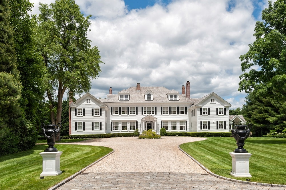 This is a look at the front of the mansion from the vantage of the driveway. You can see here the bright exteriors of the house adorned with multiple windows. Image courtesy of Toptenrealestatedeals.com.