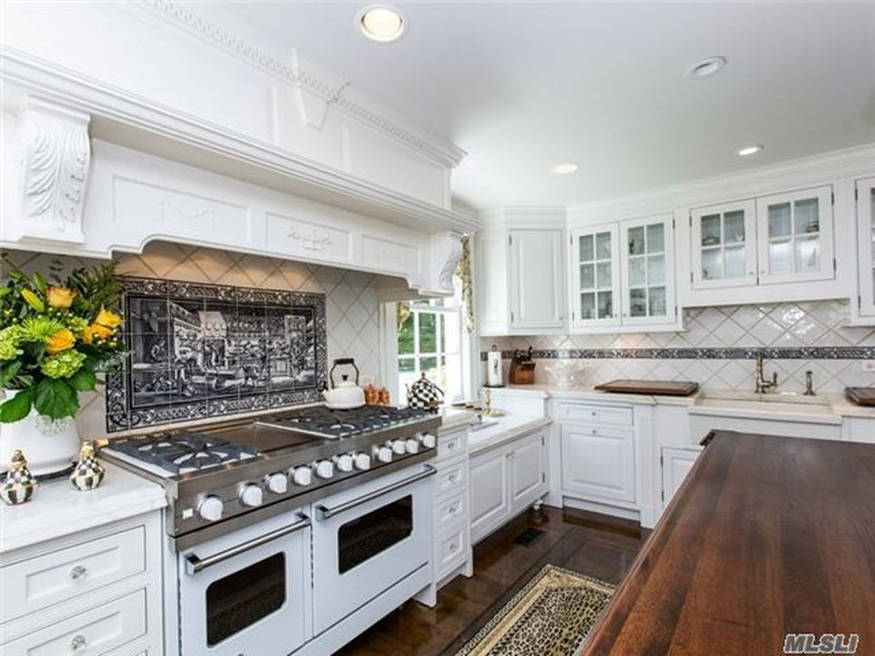 This other look at the kitchen showcases the cooking area that stands out against the white cabinetry and white vent hood. Image courtesy of Toptenrealestatedeals.com.