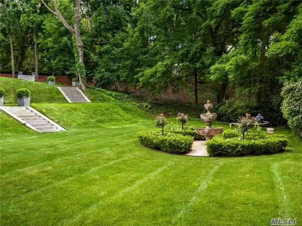 This is a look at the landscaping that has a fountain in the middle of shrubs and grass lawns. Image courtesy of Toptenrealestatedeals.com.