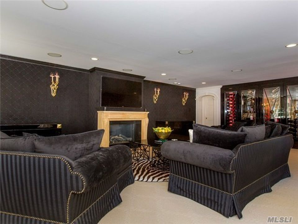 This is the living room with black cushioned sofas to match the black wall that houses the fireplace with a contrasting beige mantle. Image courtesy of Toptenrealestatedeals.com.