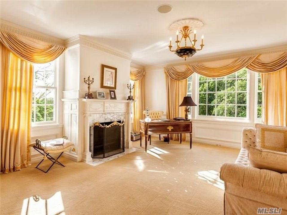 The home office has a large beige fireplace in the middle. On the side is the wooden desk by the corner windows with beige curtains. Image courtesy of Toptenrealestatedeals.com.