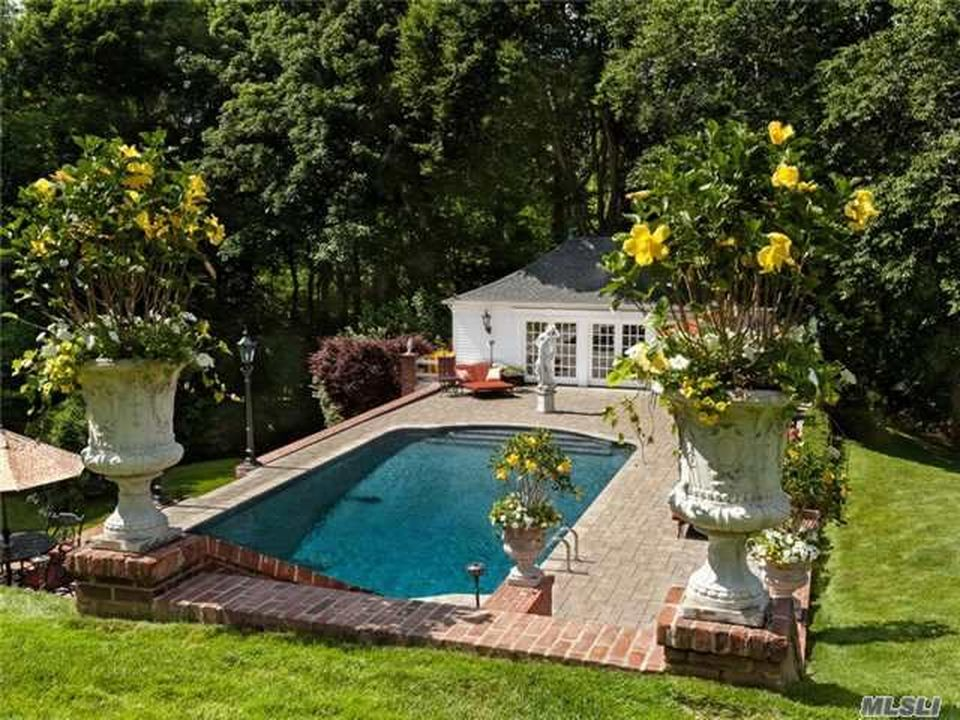 This is a look at the backyard pool from the vantage of the house. You can see here the pool surrounded by a red brick flooring leading to the pool house at the edge. Image courtesy of Toptenrealestatedeals.com.