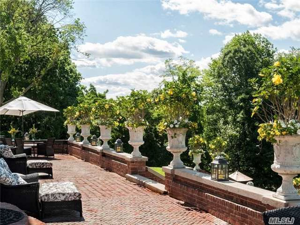 This is a look at the red brick terrace that is lined with potted plants on the side. Image courtesy of Toptenrealestatedeals.com.