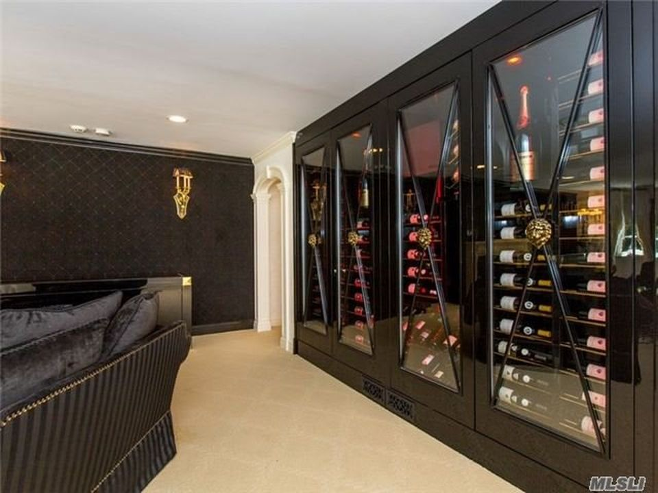 This is the wine cellar with a glass-enclosed built-in wine storage with dark tones to match the other structures of the room. Image courtesy of Toptenrealestatedeals.com.