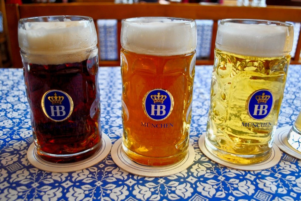 Munich Helles on coaster over a blue floral table mantel.
