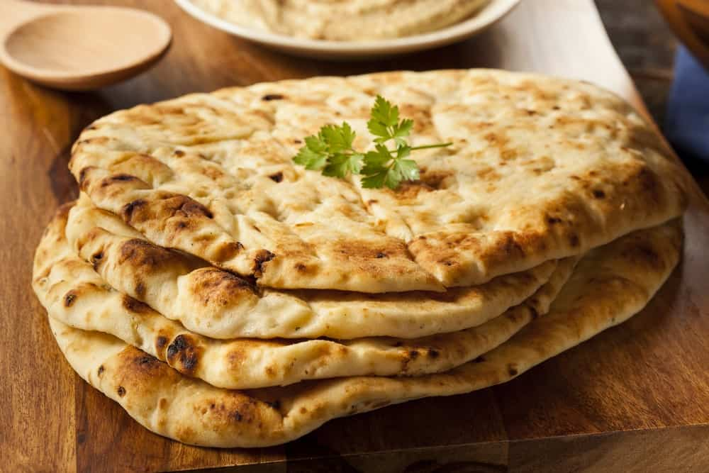 Stacked pieces of Naan bread with a parsley on top.