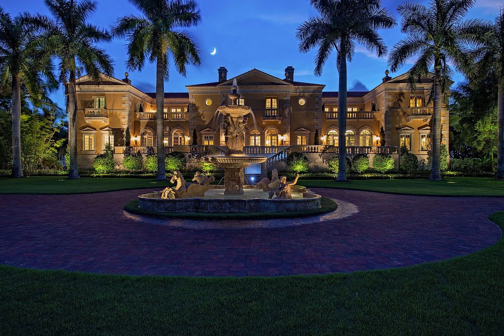 This is a nighttime view of the front of the house showcasing the warm glow of the house from interior and exterior lights that match with the lighting of the landscape that has tall tropical trees and a fountain.