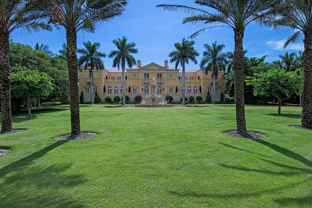 This s a look at the front of the house from the vantage of the large grass lawn. Here you can see the beige tone of the exterior walls that make it stand out against the surrounding landscape of tall tropical trees, grass lawns and shrubs. Image courtesy of Toptenrealestatedeals.com.