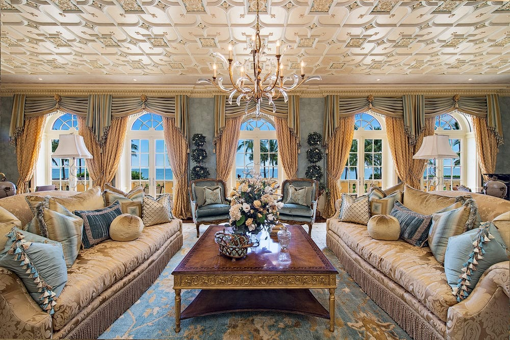 This is a look at the interior of the house showcasing the living room. You can see here the patterned ceiling with a golden hue that matches with the chandelier over coffee table that is flanked by a couple of sofas. Image courtesy of Toptenrealestatedeals.com.