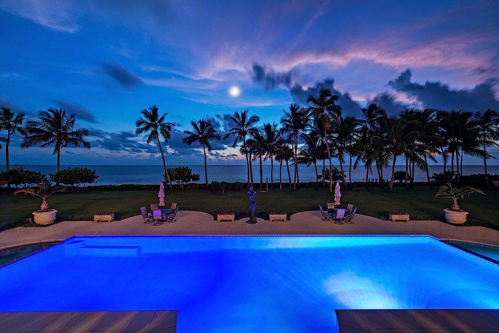 This is a closer look at the swimming pool at the back of the house. This nighttime view showcases the ethereal glow of the pool as well as the view of the ocean with silhouettes of tall tropical trees. Image courtesy of Toptenrealestatedeals.com.