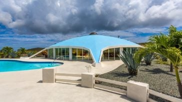 This is a front view of the dome-shaped house with glass walls. This is complemented y the surrounding landscaping of tropical trees and the large pool. Image courtesy of Toptenrealestatedeals.com.