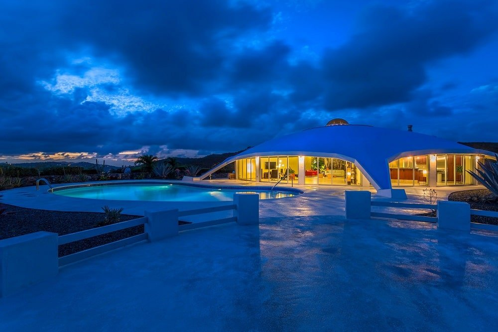 This is a nighttime view of the house exterior showcasing the ethereal glow of the swimming pool complemented by the warm glow that comes from the glass walls of the house. Image courtesy of Toptenrealestatedeals.com.