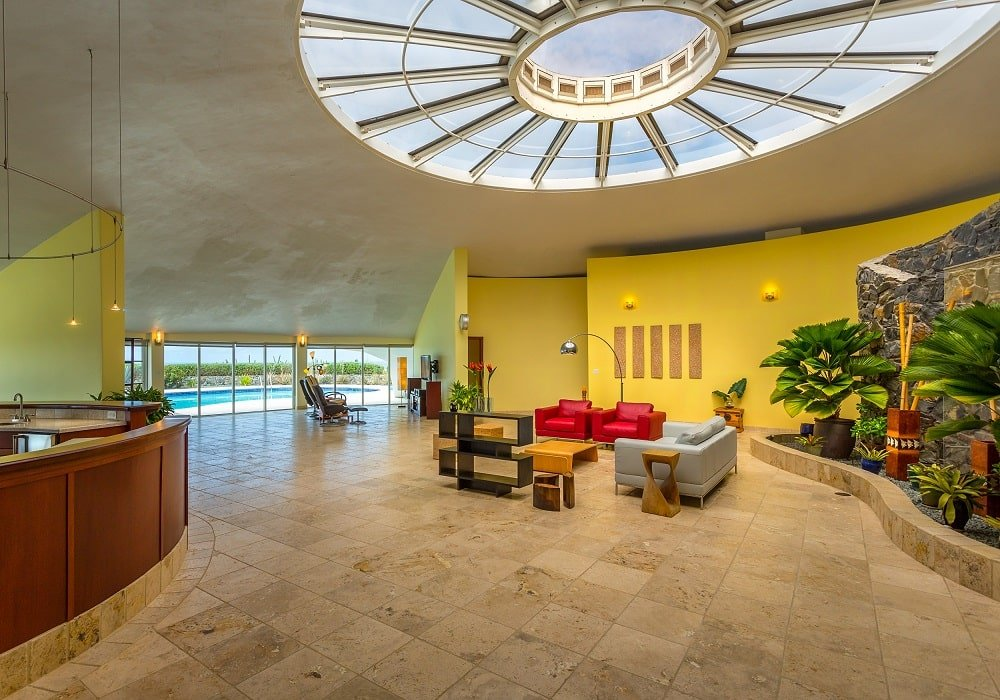 This is a look at the interiors of the house with a large circular skylight in the middle of the tall ceiling. You can see here that it has an open design showcasing the living room area in the middle adorned with a fountain and indoor garden on the side. Image courtesy of Toptenrealestatedeals.com.
