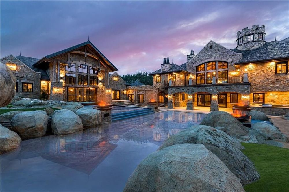 This is the back of the house that showcases a large pool adorned with decorative rocks on the side. This also gives a look at the house exteriors that are filled with warm lights and glass walls. Image courtesy of Toptenrealestatedeals.com.