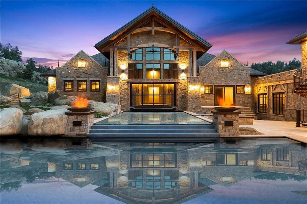 This is a closer look at the back of the house that is dominated by a large glass wall with an arch at the top. This is further augmented by the earthy exterior walls that are lit by the wall-mounted exterior lights. Image courtesy of Toptenrealestatedeals.com.