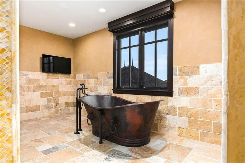This is the freestanding bathtub of the bathroom with a dark tone to it to match the window frame. These stand out against the beige tones of the floor, walls and ceiling. Image courtesy of Toptenrealestatedeals.com.