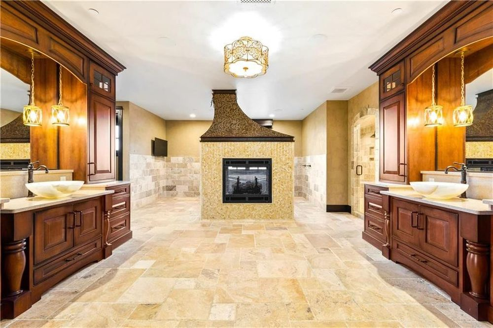 The bathroom has a couple of vanities on each side flanking a spacious open area warmed by the fireplace on the far side. Image courtesy of Toptenrealestatedeals.com.
