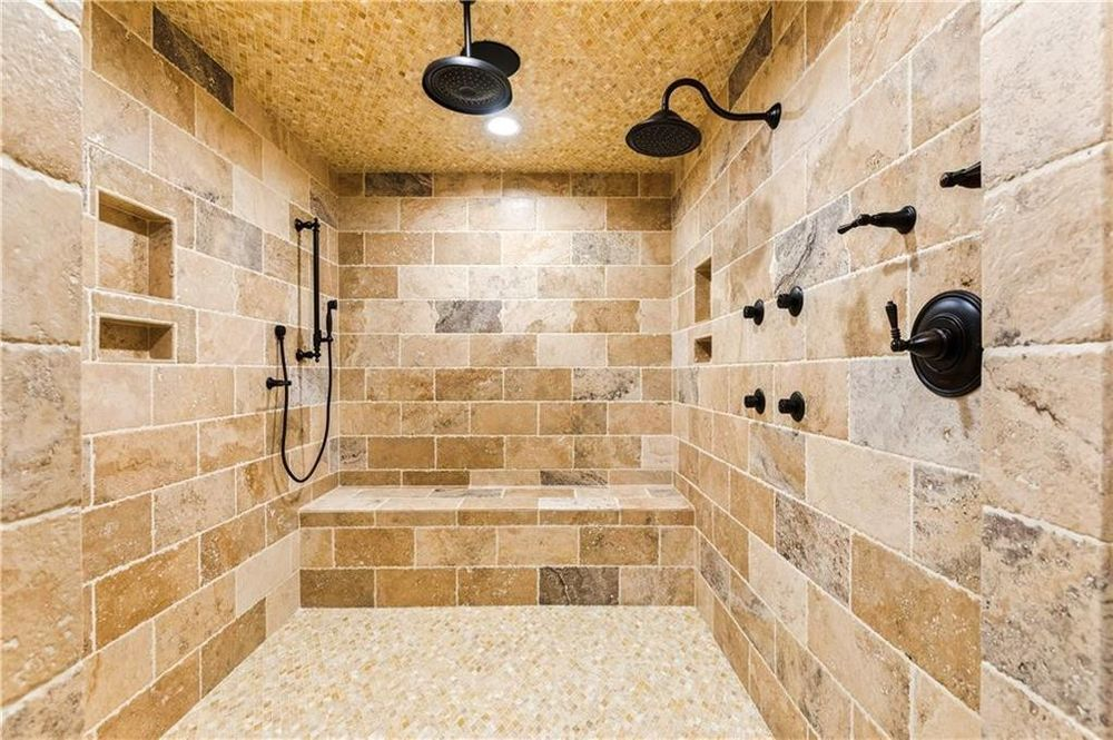 This is a close look at the spacious walk-in shower area with black fixtures to stand out against the beige tones of the walls, floor and ceiling. Image courtesy of Toptenrealestatedeals.com.