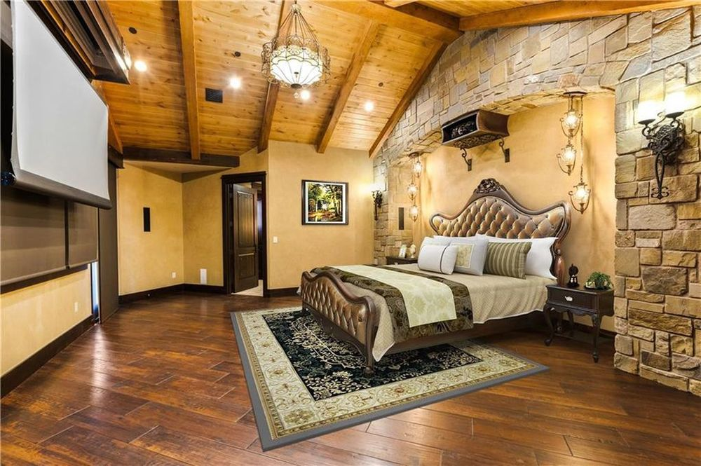 The primary bedroom has a tall wooden cathedral ceiling over the large bed with a tufted headboard. this room is equipped with a projector and a large screen. Image courtesy of Toptenrealestatedeals.com.