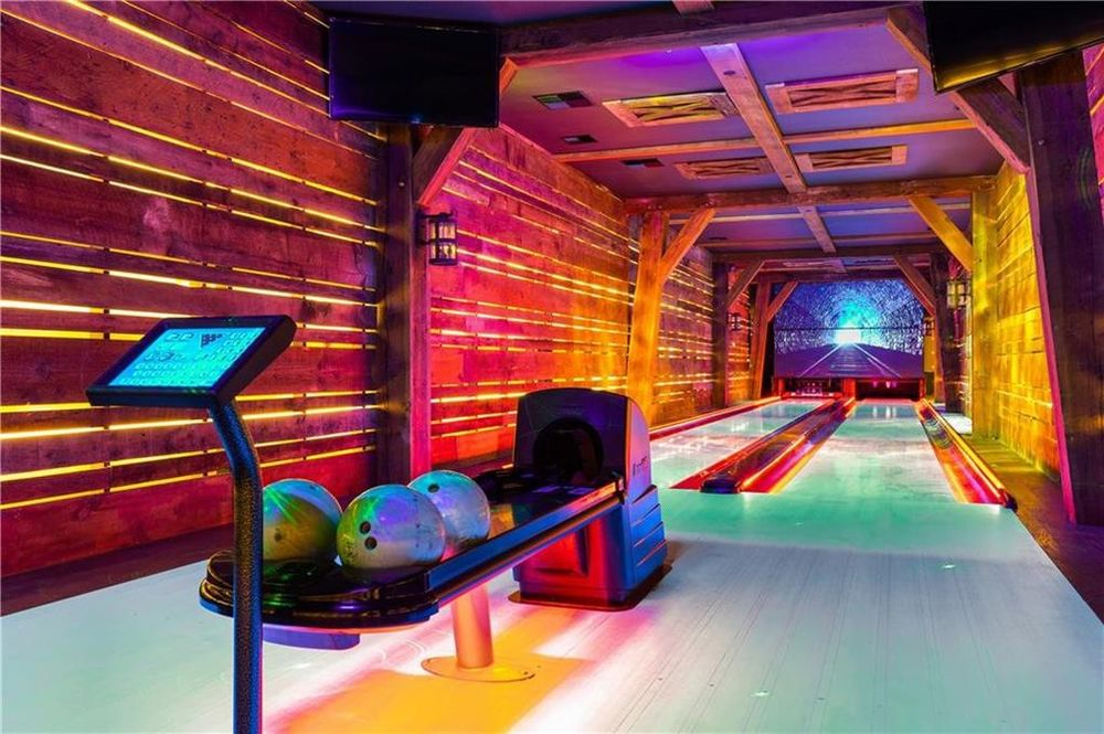 This is the two-lane bowling alley of the house with modern lighting that give the walls a colorful tone. Image courtesy of Toptenrealestatedeals.com.