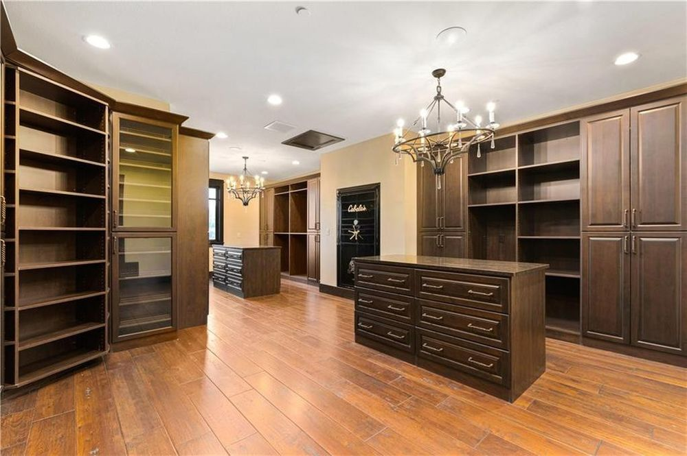 The spacious walk-in closet has various dark wooden structures with drawers, cabinets and shelves that stand out against the beige walls and white ceiling. Image courtesy of Toptenrealestatedeals.com.