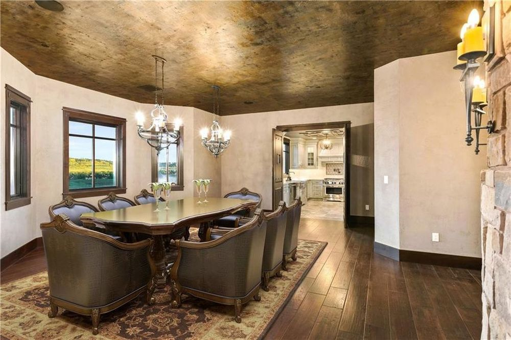 The formal dining room has a large dining table surrounded by upholstered chairs. These are topped with a couple of rows of pendant lights hanging from a dark-toned ceiling. Image courtesy of Toptenrealestatedeals.com.
