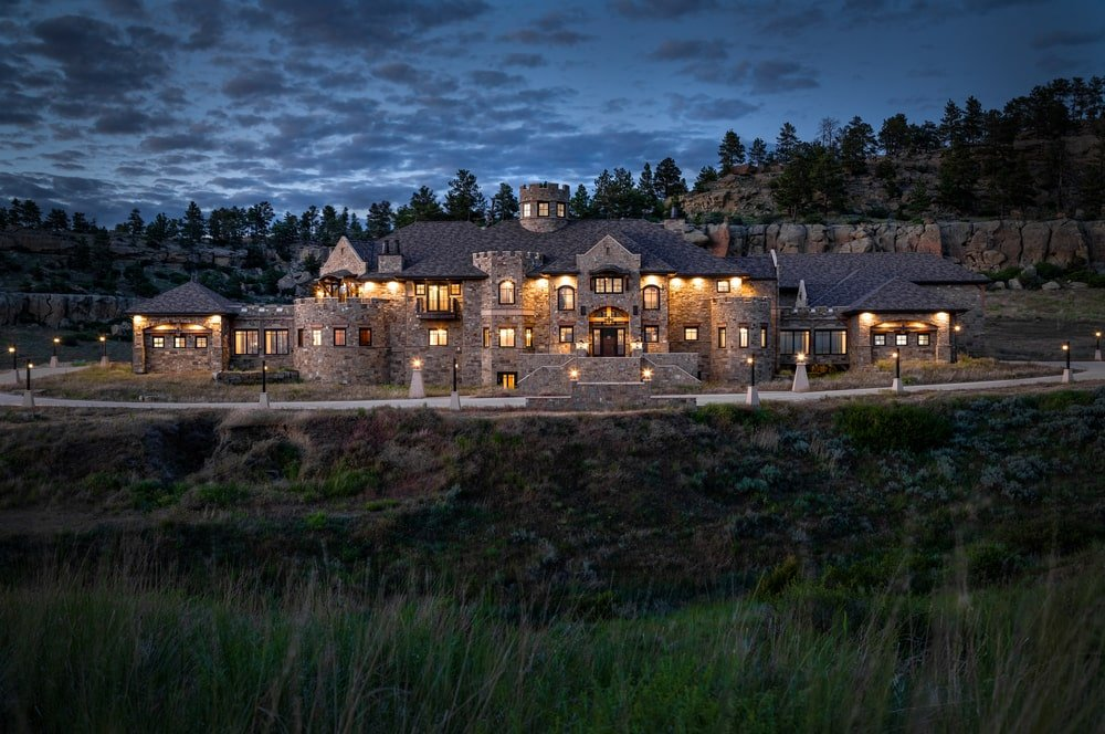 This is a nighttime view of the castle showing the warm glow that complements the earthy exterior walls and turrets of the castle. Image courtesy of Toptenrealestatedeals.com.