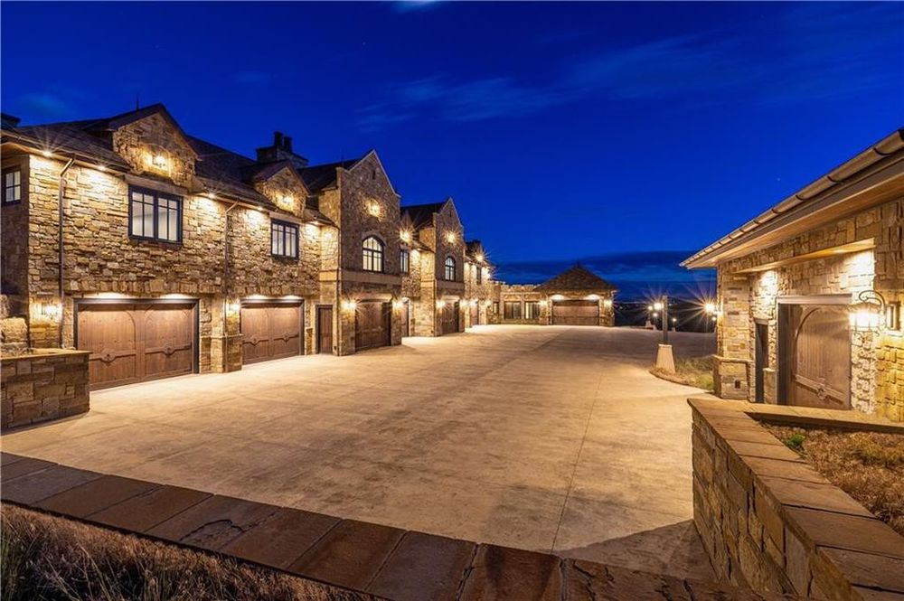 This is a look at the garages lit with warm yellow light. You can also see here the wide driveway. Image courtesy of Toptenrealestatedeals.com.