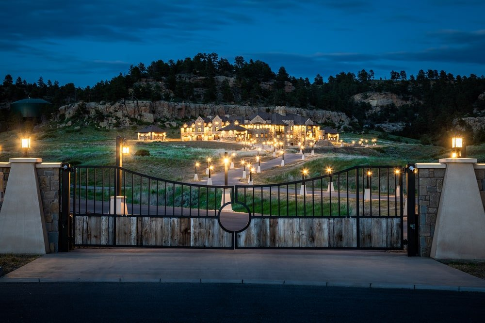 This is a nighttime view of the property from the vantage of the main gate. You can see here the spacious land adorned with the warm exterior lights. Image courtesy of Toptenrealestatedeals.com.