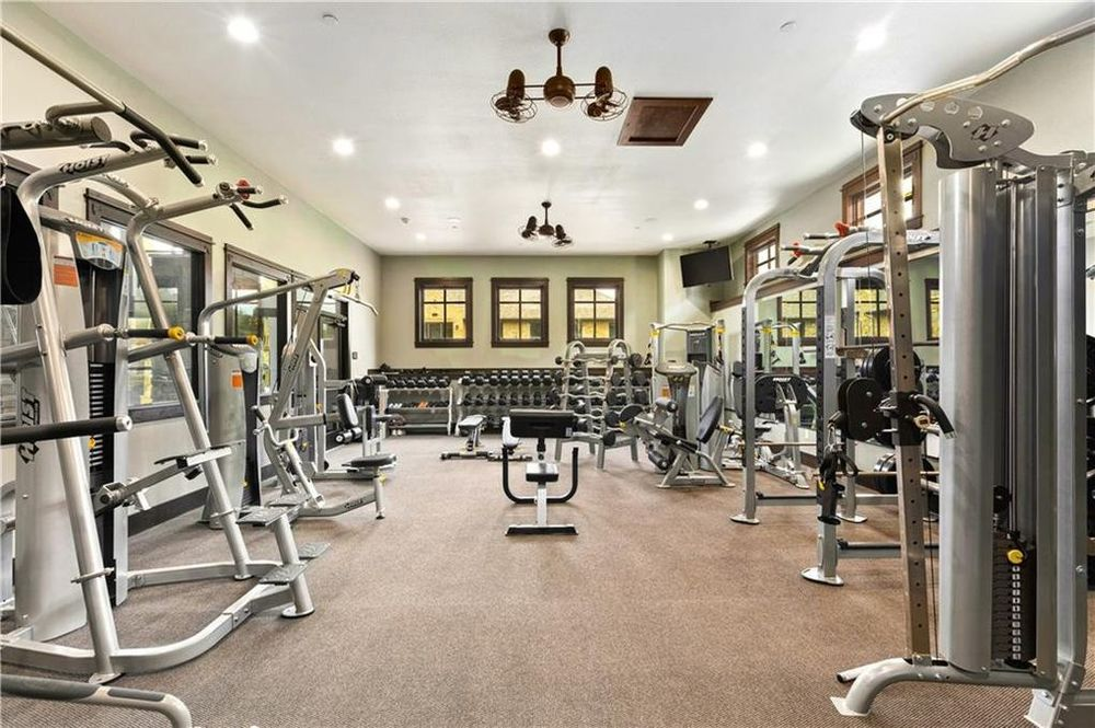 This is the fully-equipped gym of the house that is well-lit by the recessed lights of the white ceiling. Image courtesy of Toptenrealestatedeals.com.