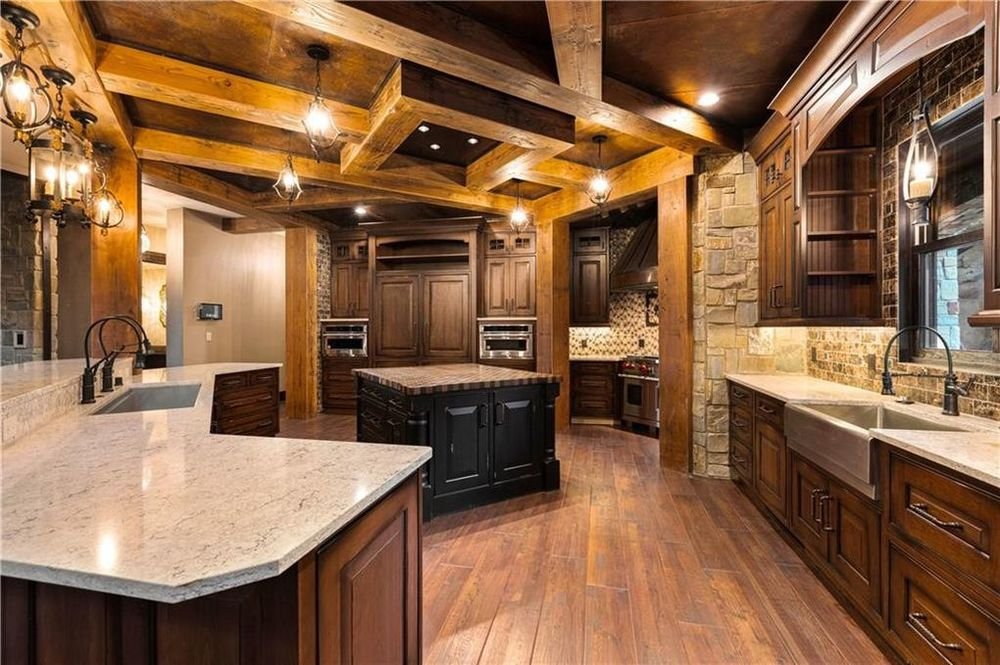 This is the main kitchen just a few steps from the living room. It has a kitchen island in the middle of the hardwood flooring. This is topped with a ceiling adorned by exposed wooden beams that connect to pillars. Image courtesy of Toptenrealestatedeals.com.